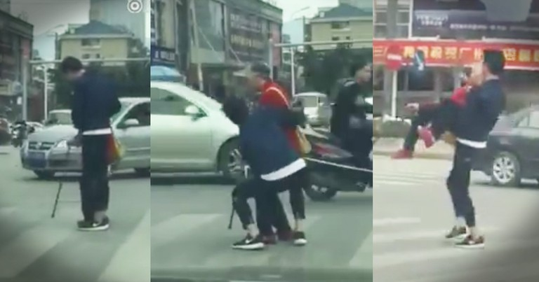 Young Man Carries Elderly Woman Across Busy Intersection